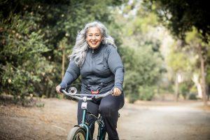 אישה בגיל המעבר רוכבת על אופניים